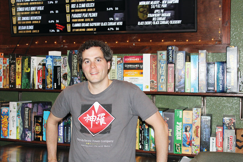 Jason Ungate, owner of the Tabletop Tap bar and arcade in Englewood, poses behind the bar.