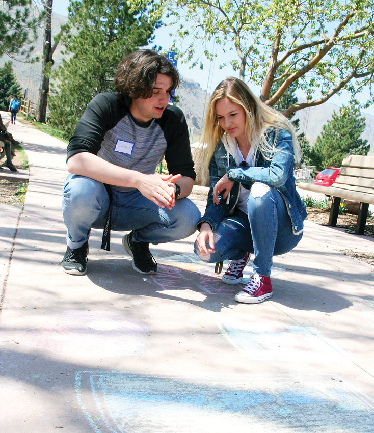 Connor Smith, a sophomore at Colorado School of Mines studying mechanical engineering, left, and Tristen Kelson, a freshman studying biochemical engineering at Mines, discuss the sidewalk chalk drawings done by Mitchell Elementary School fourth graders which will be incorporated into the Mines students are doing on data gathering.