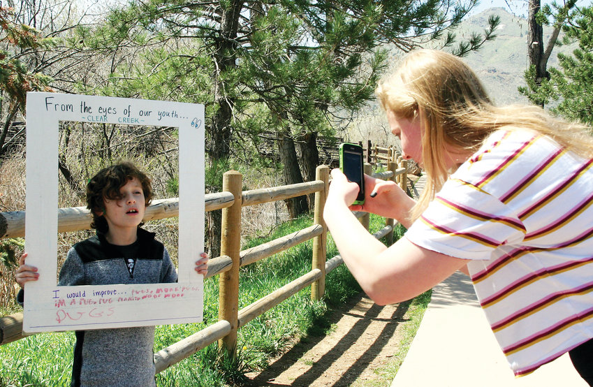 Erin Keeney, a freshman at the Colorado School of Mines, takes a picture of Oliver George, a fourth grader at Mitchell Elementary School, as he explains what some of his ideas for Clear Creek would be in an activity on April 23.