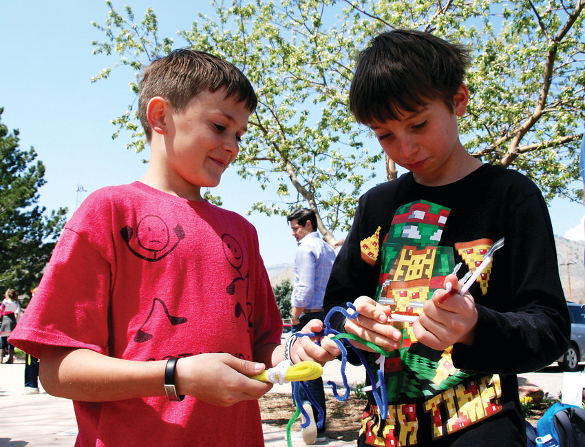 Ansel Champlin, left, and Simon Kosnak, both fourth graders at Mitchell Elementary School, build a bridge out of pipe cleaners on April 23, to provide a visual for Colorado School of Mines students for a class project on data gathering.