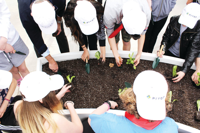 Students from the Girls Athletic Leadership Schools plant lettuce and kale in their new gardening space on campus. The school is using the gardens to teach nutrition.