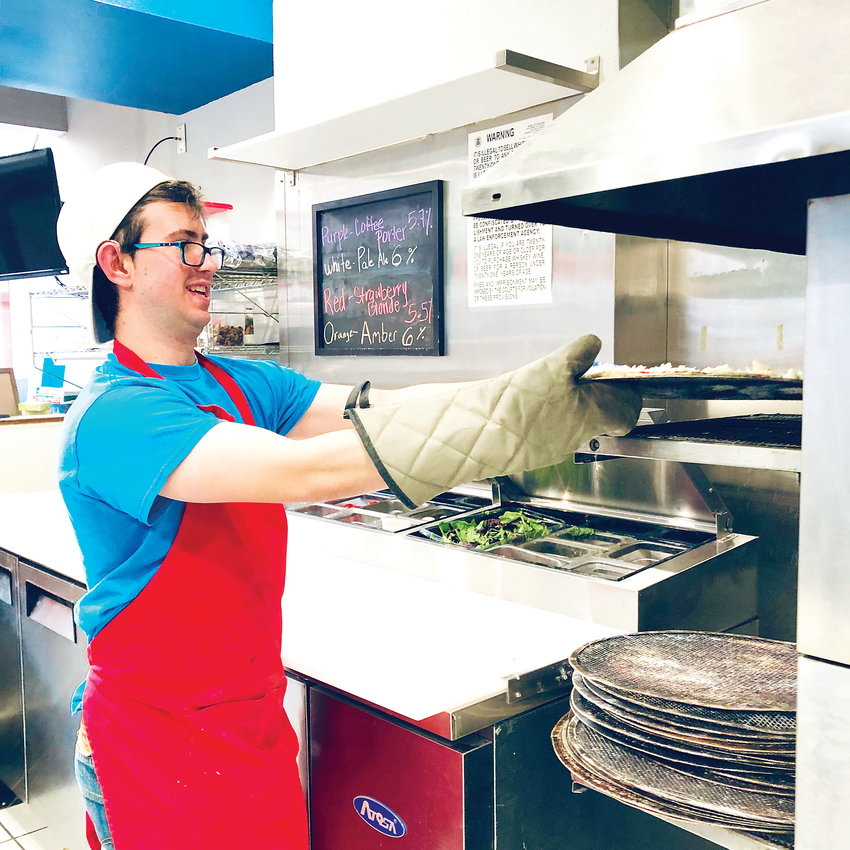 Tony Saponaro, 28, places a pizza in the oven while on the clock at Pizzability.