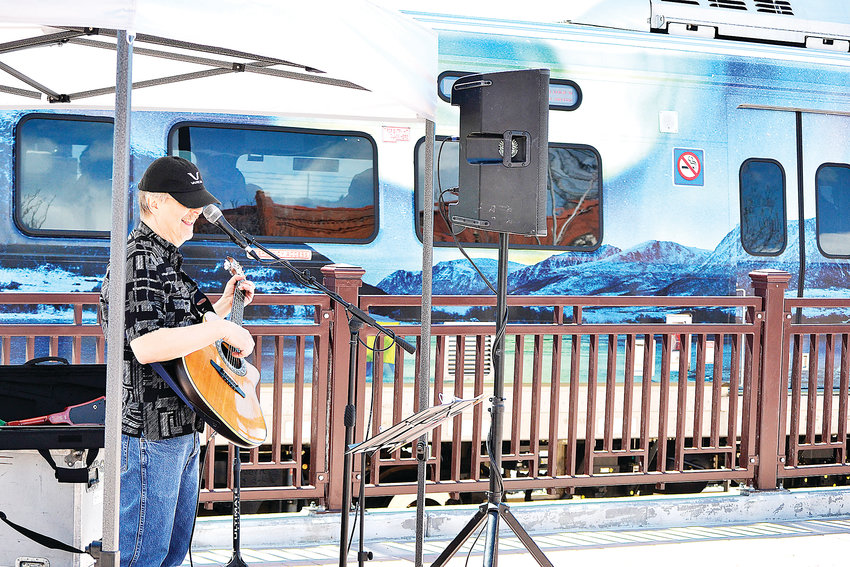 Jamie Krutz sings songs about trains as the G-Line commuter rail passes behind him. Krutz was one of several musicians to perform throughout the day Saturday, April 27, to celebrate the train's opening.