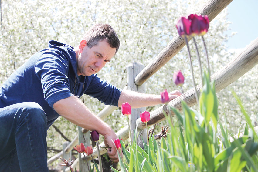 Scott Stroup touches up his flowerbed along the Crabapple Route near Heritage High School.