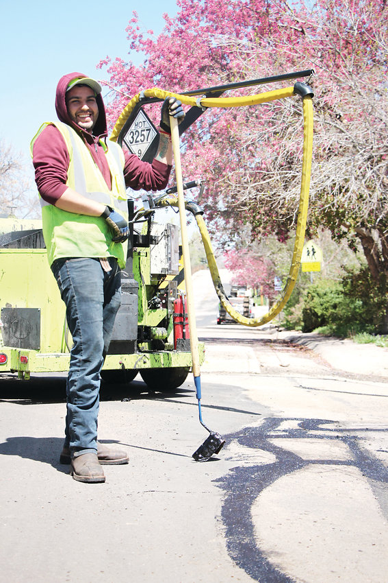 Jorge Rodriguez of Vance Brothers Construction lays down tar in cracks in the road along the Crabapple Route.