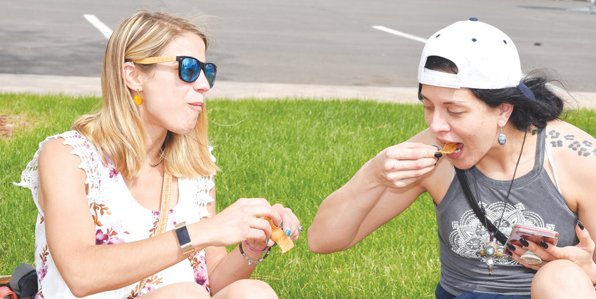 Kristina Nicol, of Johnstown, left, and Stephanie Brus, of Greeley, enjoy some chips and dip at the opening day of the Northglenn's Food Truck Carnival in 2018. The event returns to the Northglenn Community Center May 10-12.