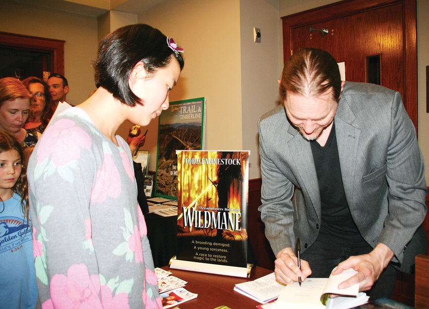 Sophie Anderson, an eighth grader at Bell Middle School in Golden who won a first-place award in the Jeffco Writing Challenge, gets her book signed by the fantasy author Todd Fahnestock on May 3 following the award ceremony.