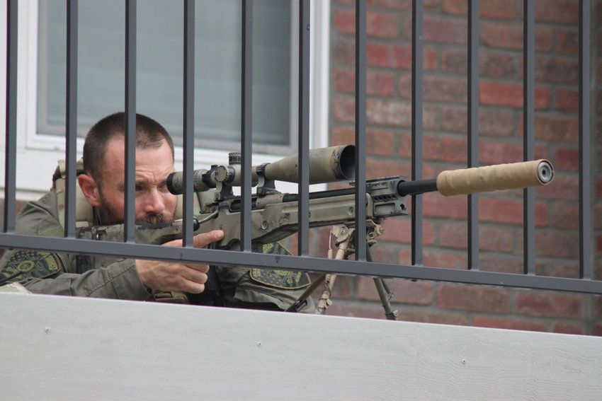 An Arapahoe County sheriff's deputy on the balcony of an apartment building across the street from the school trains his weapon on one of the doorways of the school at about 3 p.m. Tuesday.