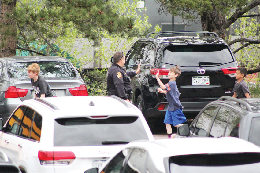 Kids high-five an officer as they leave the bus to be reunited with their parents at North Ridge Recreation Center in Highlands Ranch May 7.