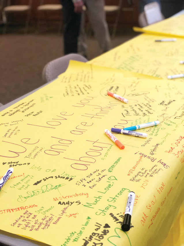 STEM students mark words of support on a poster at a May 8 service at St. Andrews United Methodist Church. The service was one of several in the community but the only one specifically for STEM families.