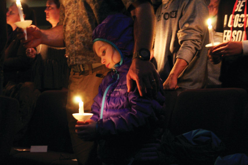 A girl holds a candle during the prayer service at Mountainview Church in Highlands Ranch May 8, memorializing the victims of the STEM School shooting May 7.