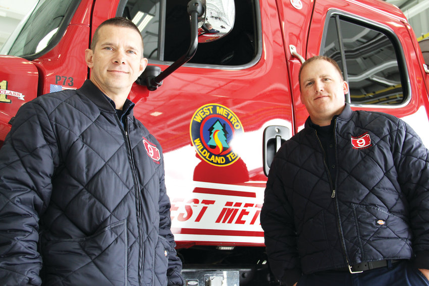 Firefighter Shawn Botsford, left, and Tony Lodice, engine boss for West Metro Fire Rescue, stand next to a West Metro truck May 7 at Centennial Airport after Colorado's 2019 wildfire outlook event. Botsford and Lodice are on West Metro's wildfire team.