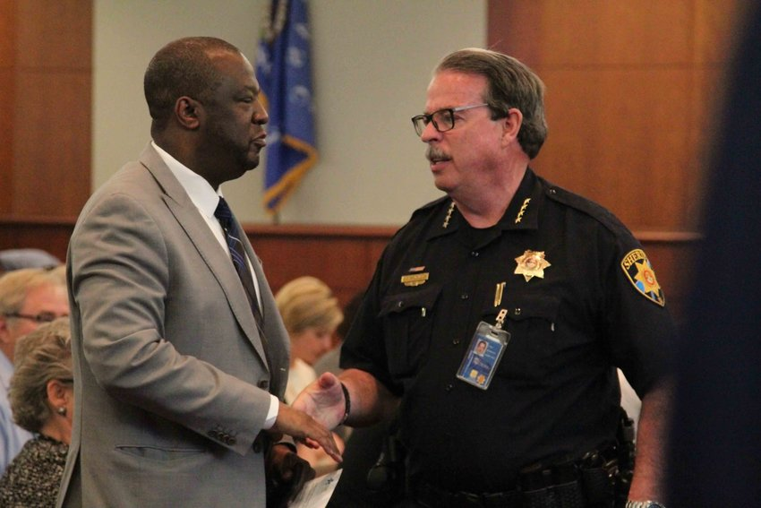 Douglas County School District Superintendent Thomas Tucker, left, and Sheriff Tony Spurlock shake hands at a special work session for the Douglas County Board of Commissioners on May 13.