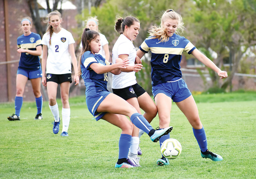Wheat Ridge sophomores Whitney Clark, left, and Emelia Probst (8) converge on Holy Family sophomore Jaelan Giron during the first half May 11 at Lakewood Memorial Field.