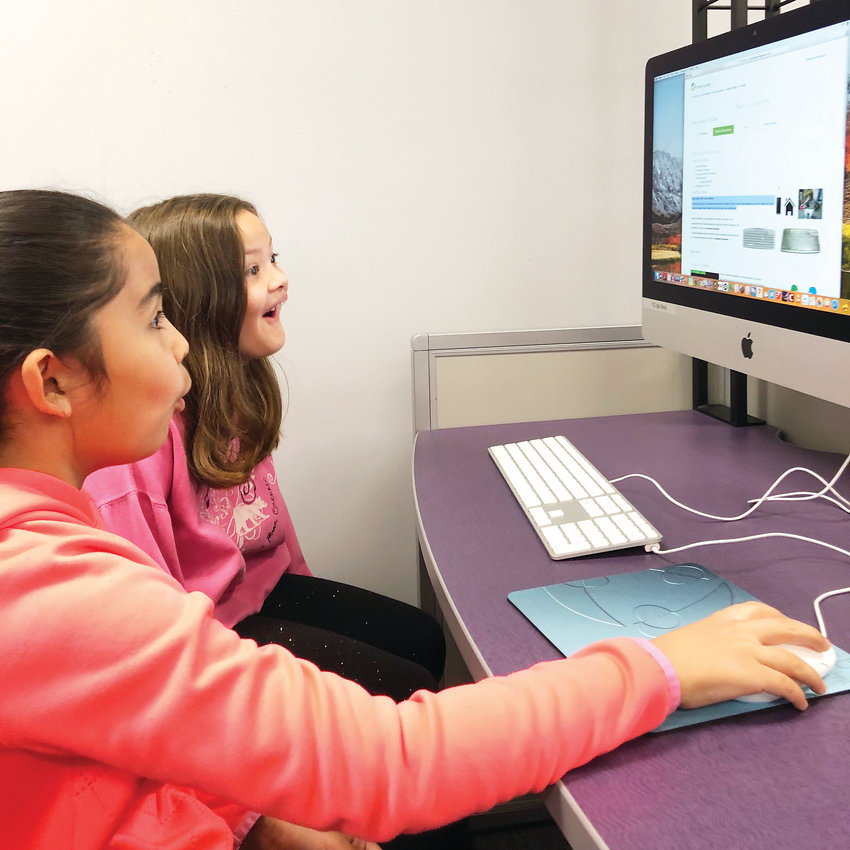 Thomson third-graders Haleigh Roybal, left, and Scarlett Newman explore a new website during a visit to the school's STEM lab.