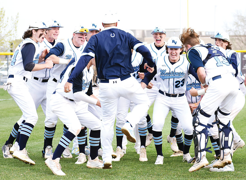 Ralston Valley coach Brad Madden jumps into the celebration with his players after a 4-0 victory over Columbine on May 10 at Nate Jurney Field. The win wrapped up the Class 5A Jeffco League title for the Mustangs.