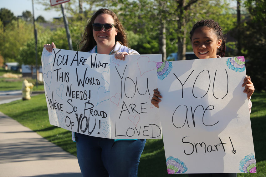 "Krystal Jensen, left, and her 12-year-old daughter Kierra welcome STEM students back to school on May 15. About a week earlier, the school experienced a shooting that left one student dead and eigth others injured. ""They need all the love they can get right now,"" said Krystal, who homeschools her daughter."