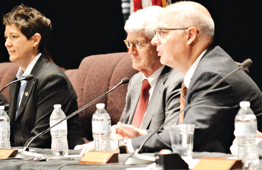 Justices Monica Marquez, left, and Chief Justice Nathan B. Coats listen while colleague Brian Boatright answers a student question May 7 at Westminster High School.