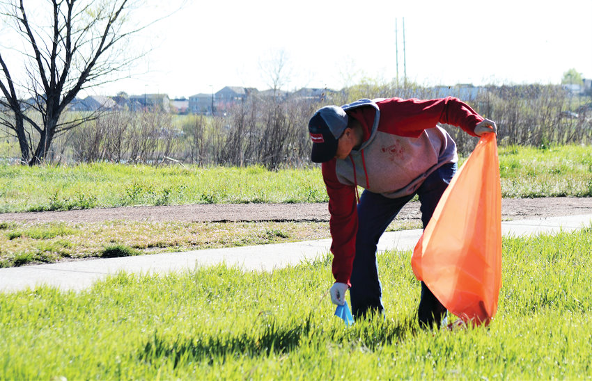 Jack Brenckle of Brighton stoops to pick up a piece of trash along the Big Dry Creek Trail, part of the city of Westminster's Community Pride Day May 11.  An estimated 1,000 people showed up at Westminster trails and parks to collect trash as part of the day.