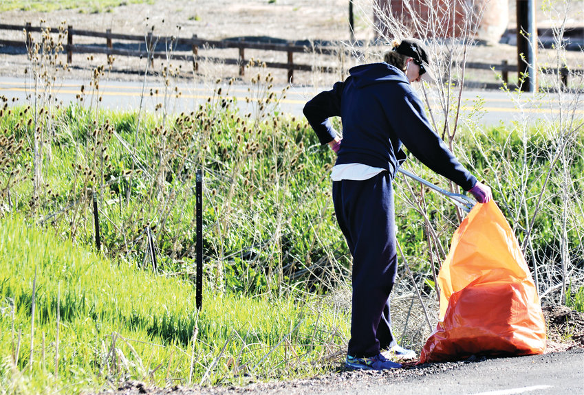Cynde Fleck of Westminster bags a piece of trash she collected along 108th Avenue at Old Wadsworth May 11. Fleck was one of an estimated 1,000 volunteers that spread out around the city to pick up trash during Westminster Community Pride Day.