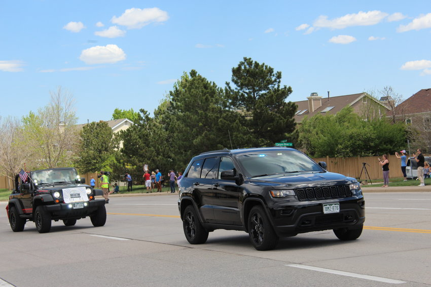 An undercover Douglas County Sheriff Jeep Cherokee leads a processional of Jeeps through Highlands Ranch to a celebration of life ceremony at Cherry Valley Community Church.