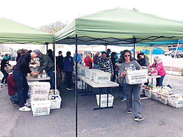 About 100 volunteers from the Christian Action Guild and the Golden Lions Club sort through the donations received from this year's U.S. Postal Service's annual Stamp Out Hunger Food Drive, which happened on May 11.