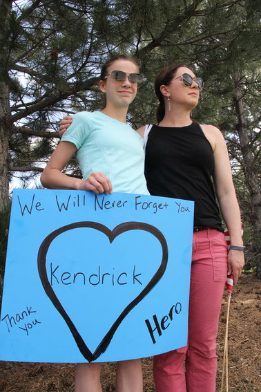 "A mother and daughter, who did not want to be named, stand along the road awaiting a motorcade of Jeeps driving to Cherry Hills Community Church for a May 15 memorial service for Kendrick Castillo. The sign they brought read, ""We will never forget you,"" ""Thank you"" and ""Hero."""