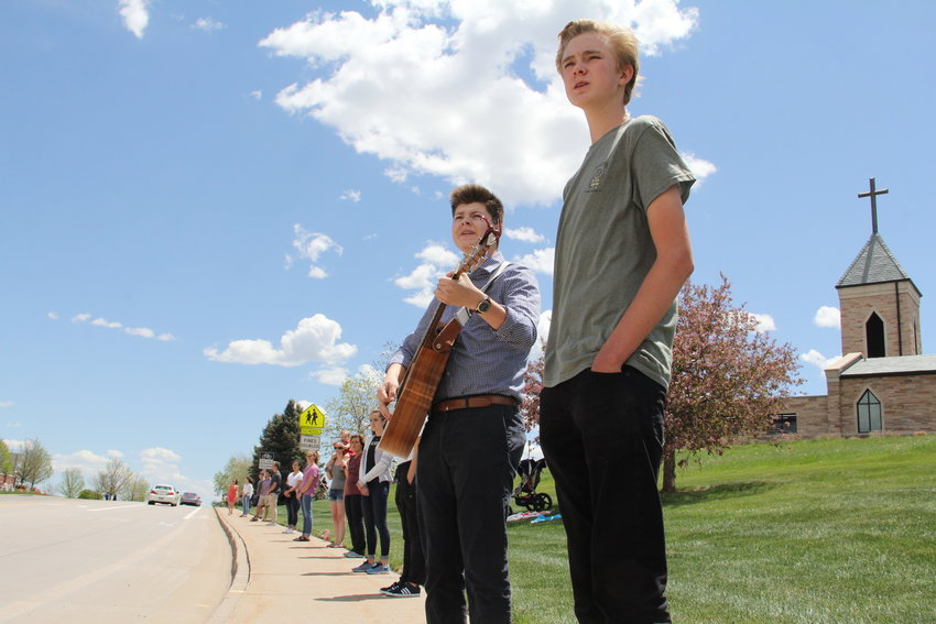Bendor Shallow, right, and Connor LeFebre, with the guitar, stand in a line of Valor Christian High School students awaiting a motorcade to arrive at a May 15 memorial service for Kendrick Castillo. Shallow and LeFebre are on student council at Valor, which stands across the street from Cherry Hills Community Church, the service's venue.