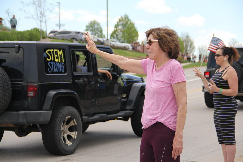 "Bonnie Alexander, 68, waves a peace sign at drivers in a motorcade of more than 200 Jeeps and some other vehicles toward a May 15 memorial service for Kendrick Castillo. Castillo ""was an angel in our midst,"" said Alexander, a Highlands Ranch resident."