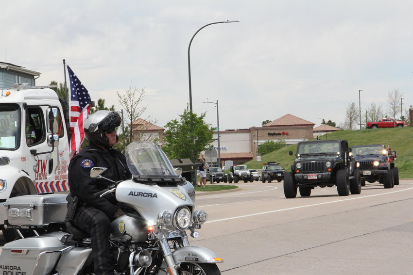 An Aurora police officer sits to keep traffic stopped as a motorcade of more than 200 Jeeps drove by for a May 15 memorial service for Kendrick Castillo.