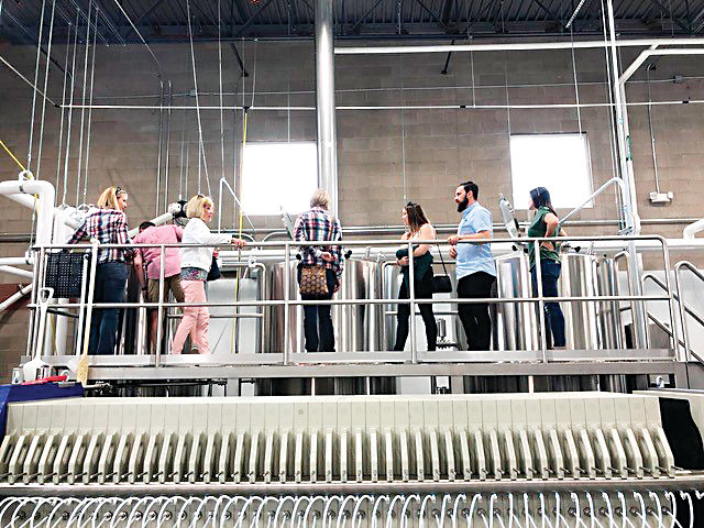 A group of people check out Holidaily's new mash press brewing system on May 4 during a tour of Holidaily 2.0, the brewery's new production facility at 820 Brickyard Circle in Golden.