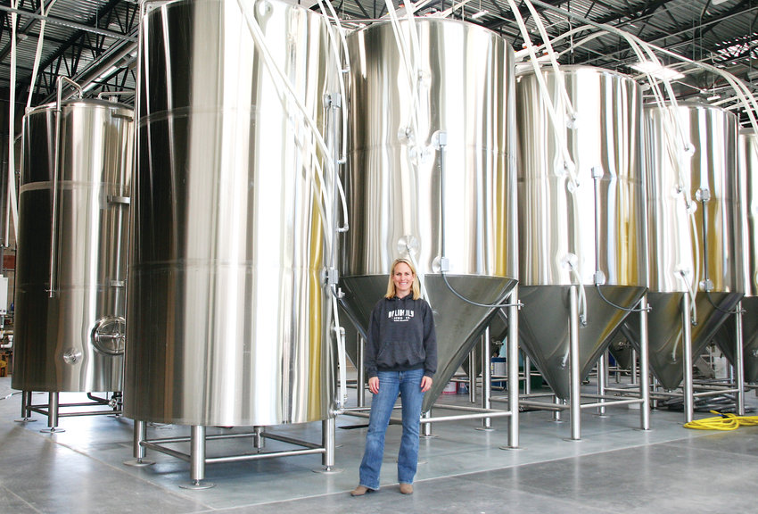 Karen Hertz, owner and founder of Holidaily Brewing Company, stands in front of the brewery's 60-barrel tanks inside Holidaily 2.0, the brewery's new production facility at 820 Brickyard Circle in Golden.