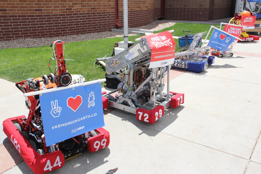 Robots line the walkway to Cherry Hills Community Church May 15 during a memorial service for Kendrick Castillo. The robots bore signs including Castillo's name and heart symbols.