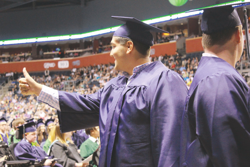 A graduate gives a thumbs up before receiving his diploma.