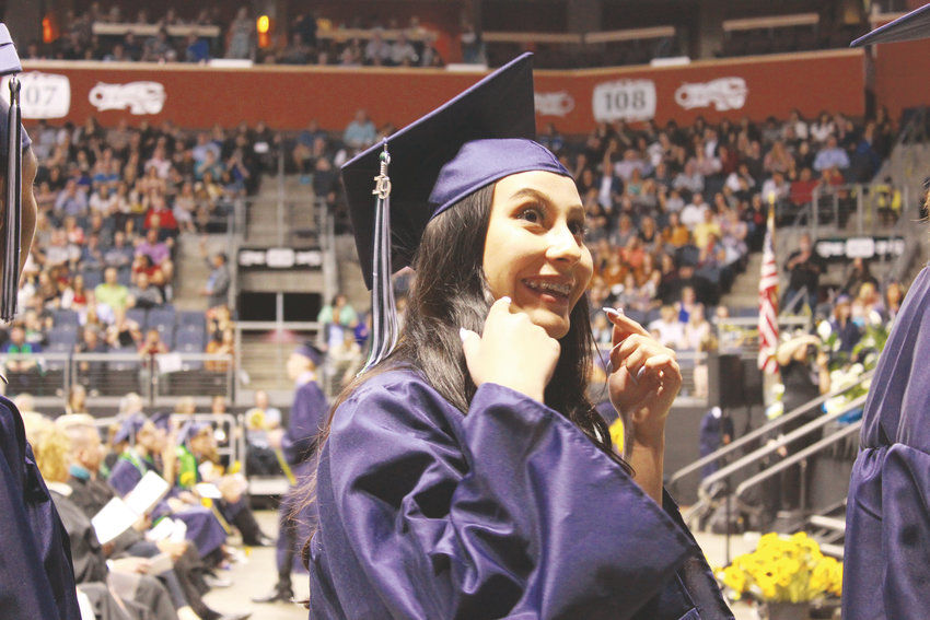 A Standley Lake High School graduate smiles at a loved one before recieving her diploma.