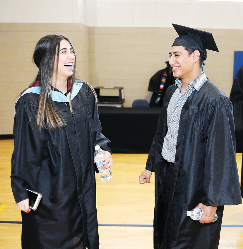 Westminster High graduates Andrya Hernandez-Robles, left and Miguel Villalobos, share a light moment prior to formal graduation ceremonies, at the First Bank Center in Broomfield, Saturday, May 18. 413 seniors received diplomas.