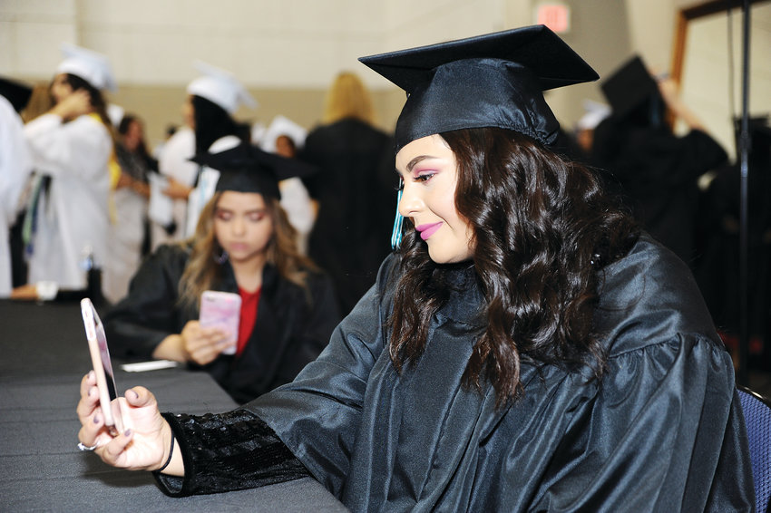 Westminster High graduate Monica Andrade Dominguez, checks her cell phone, prior to the start of formal graduation ceremony May 18 at the First Bank Center in Broomfield.