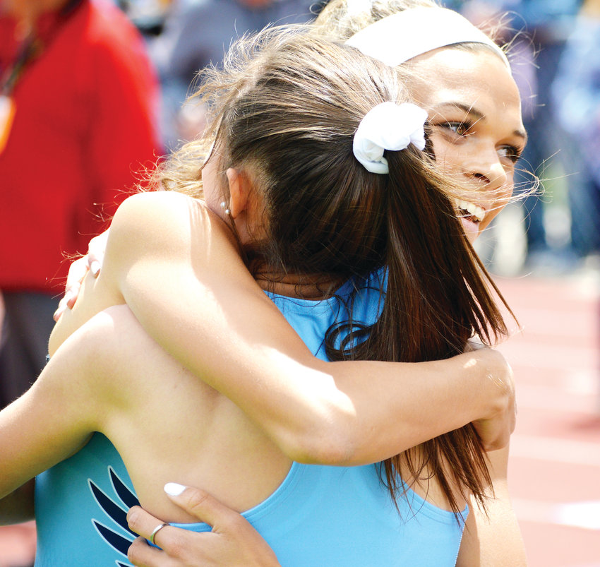Valor Christian's Anna Hall hugs teammate Maddy Ortman after the finish of the 300 meter hurdles race. Hall won and Ortman was fourth.