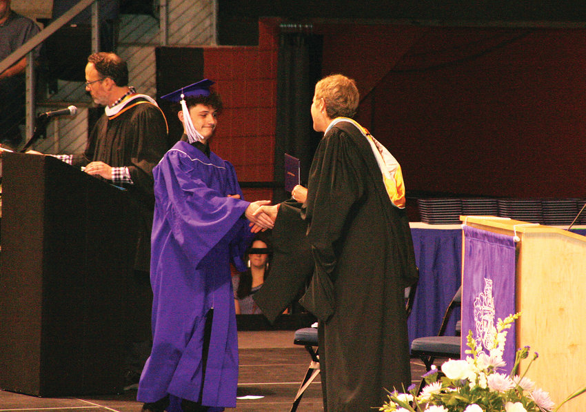 Samuel John Lombardi Jr. gets his diploma handed to him during Arvada West High School's 2019 commencement ceremony on May 17.