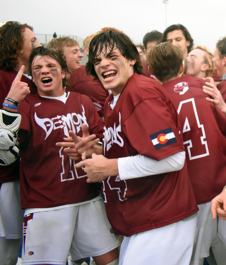 Golden seniors Brady desGarennes, left, and Garrett Landmark celebrate after the Demons won the Class 4A boys lacrosse state championship over defending state champion Cheyenne Mountain on Monday, May 20, at All-City Stadium.