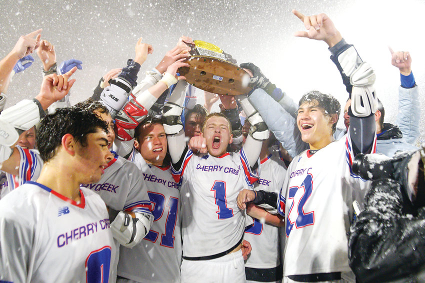 Cherry Creek's boys lacrosse team raises the Championship trophy as they celebrate their 12-7 victory over Kent Denver in the 5A State Final on May 20 at All City Field.
