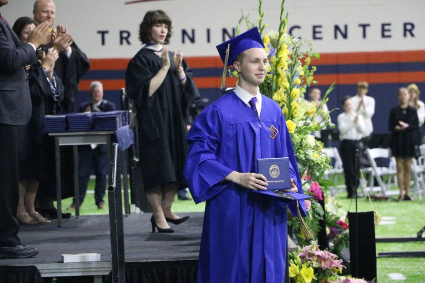 STEM School Highlands Ranch graduate Jordon Monk accepts Kendrick Castillo's diploma at a May 20 commencement ceremony at the Broncos Training Facility. Castillo was Monk's best friend.