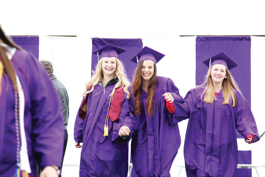 The girls hold hands during the 2019 graduation ceremony for Douglas County High School.