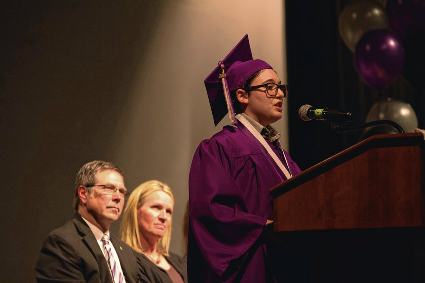 "David Funk, one of Options' ""outstanding seniors,"" speaks at graduation, as Options Principal Greg Sumlin and Dean Susan Davis look on."