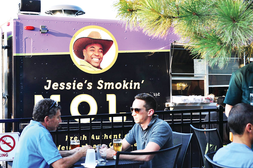 Patrons eat outside the food truck, Jessie's Smokin' NOLA, which serves food inspired by New Orleans cuisine.