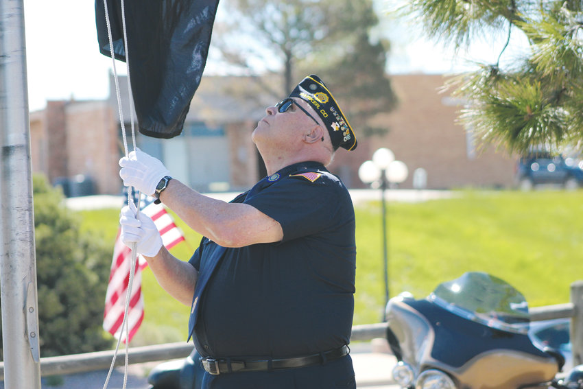A member of the Parker American Legion Post No. 1864 raises the U.S. flag at the start of the annual Memorial Day ceremony at the Parker Cemetery May 27.