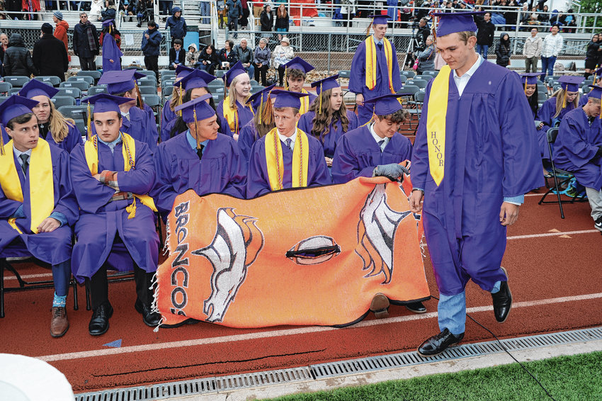 Holy Family graduates use a football blanket to try and stay warm, during May 23 graduation ceremonies at Holy Family High School in Broomfield. Despite the cold, damp weather, 163 Holy Family seniors received diplomas.