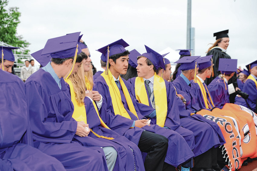 Holy Family graduates, including Zach Becker, center, take their seats at Mike Gabriel Stadium for the school's 94th annual commencement May 23, at Holy Family High School in Broomfield.