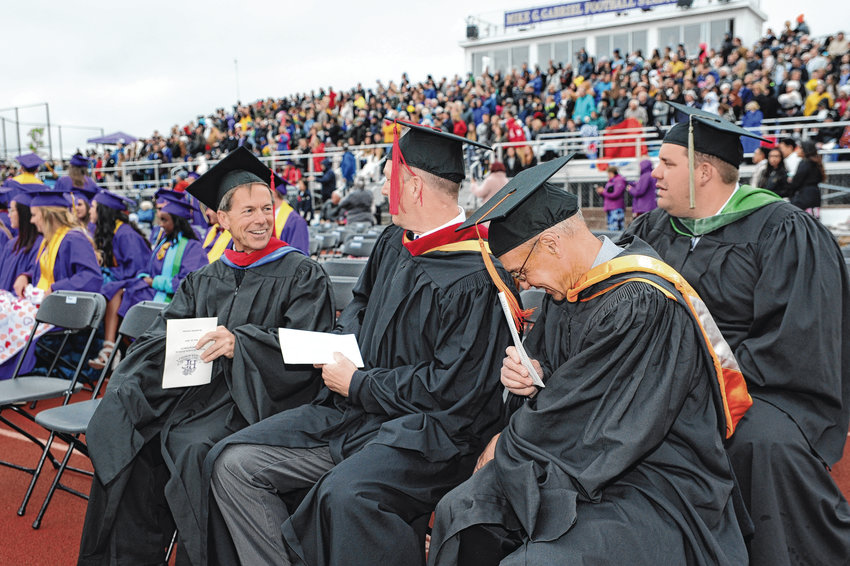 Holy Family faculty, including theology teacher David Good, left, take their seats for the school's 94th annual commencement May 23, at Holy Family High School in Broomfield.
