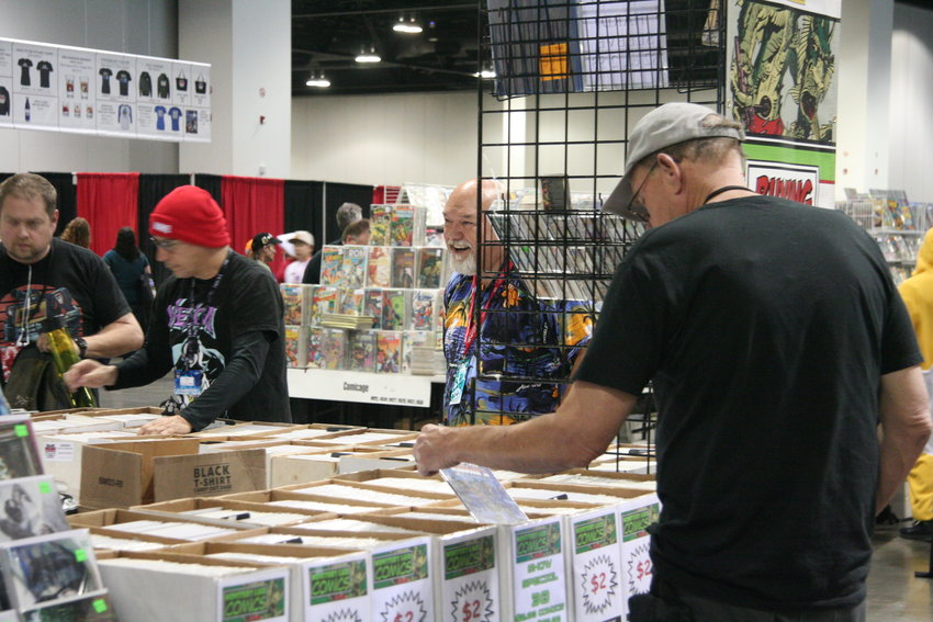 Though this year the name changed to Denver Pop Culture Con, comics are still the keystone of the annual event. As day two gets underway, early shoppers at one of the many comic vendors search out new books for their collections.